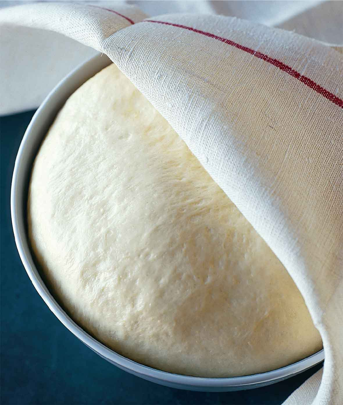 A ball of rising semolina pizza dough in a round metal tin, partially covered by a kitchen towel.