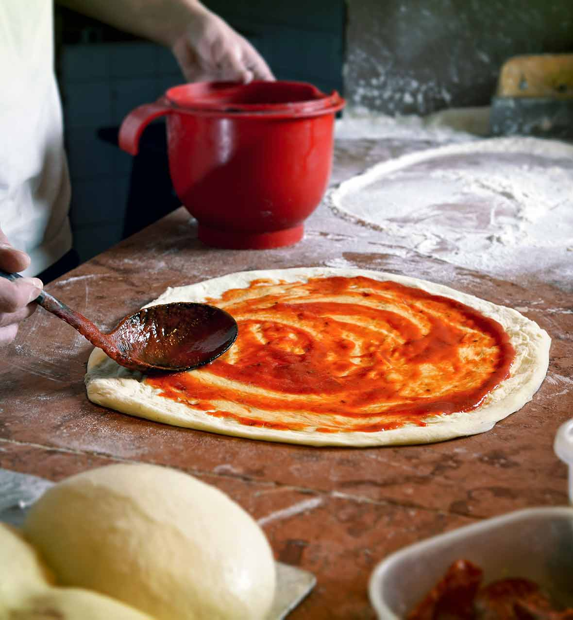 A wooden spoon spreading simple pizza sauce on a round of pizza dough.