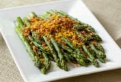 Asparagus with brioche crumbs piled on a white serving platter.