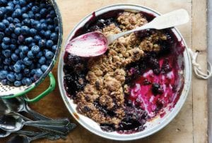 A half-eaten dish of blueberry crumble with a spoon resting on top and a colander of fresh blueberries beside it.