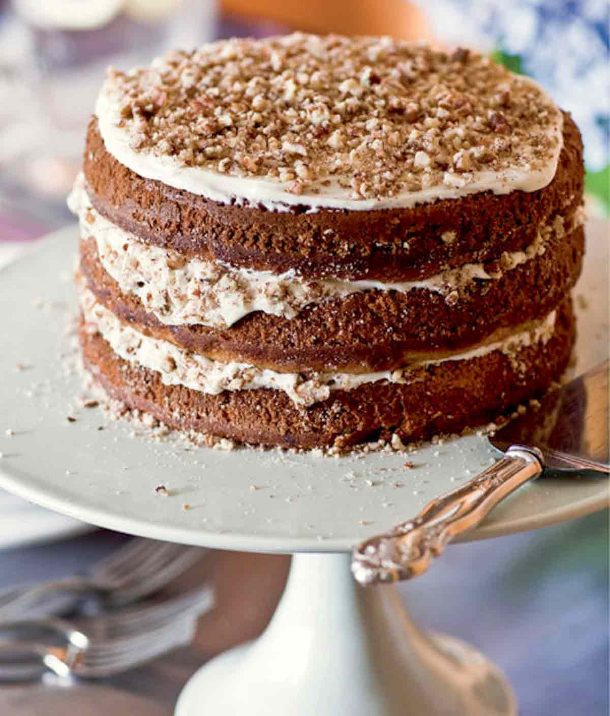 A three-layer hummingbird cake with a cake server beside it.