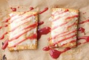 Two homemade toaster tarts on a sheet of parchment drizzled with glaze.