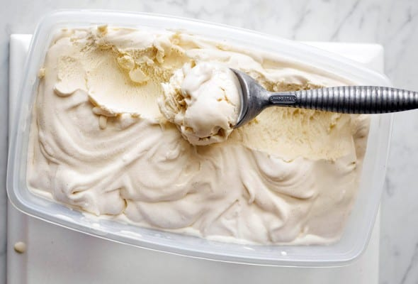 A plastic container filled with vanilla bean ice cream with a metal ice cream scoop resting inside.