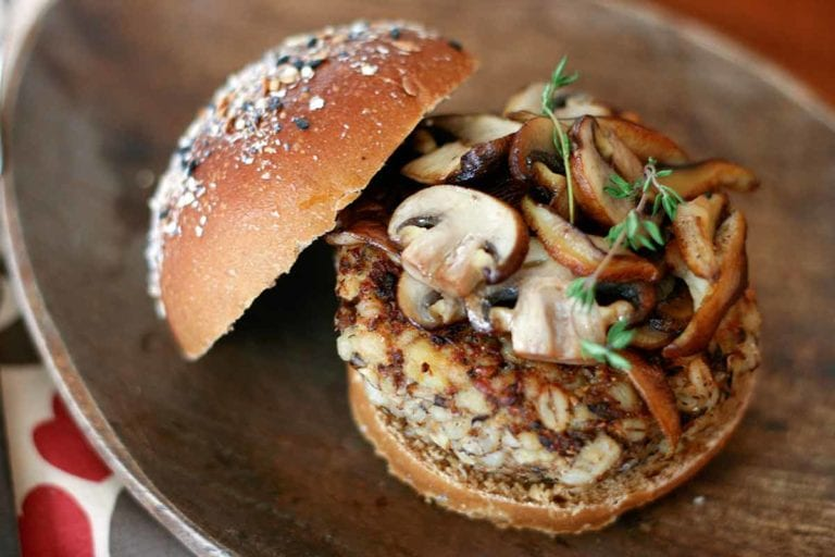 A veggie burger topped with mushrooms and thyme on an oval plate.
