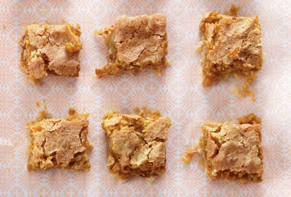 A white baking dish with a piece of patterned parchment and 15 squares of coconut blondies.