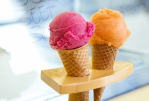 Two sugar cones, one filled with a scoop of cantaloupe sorbet, the other with a scoop of hibiscus beet sorbet.