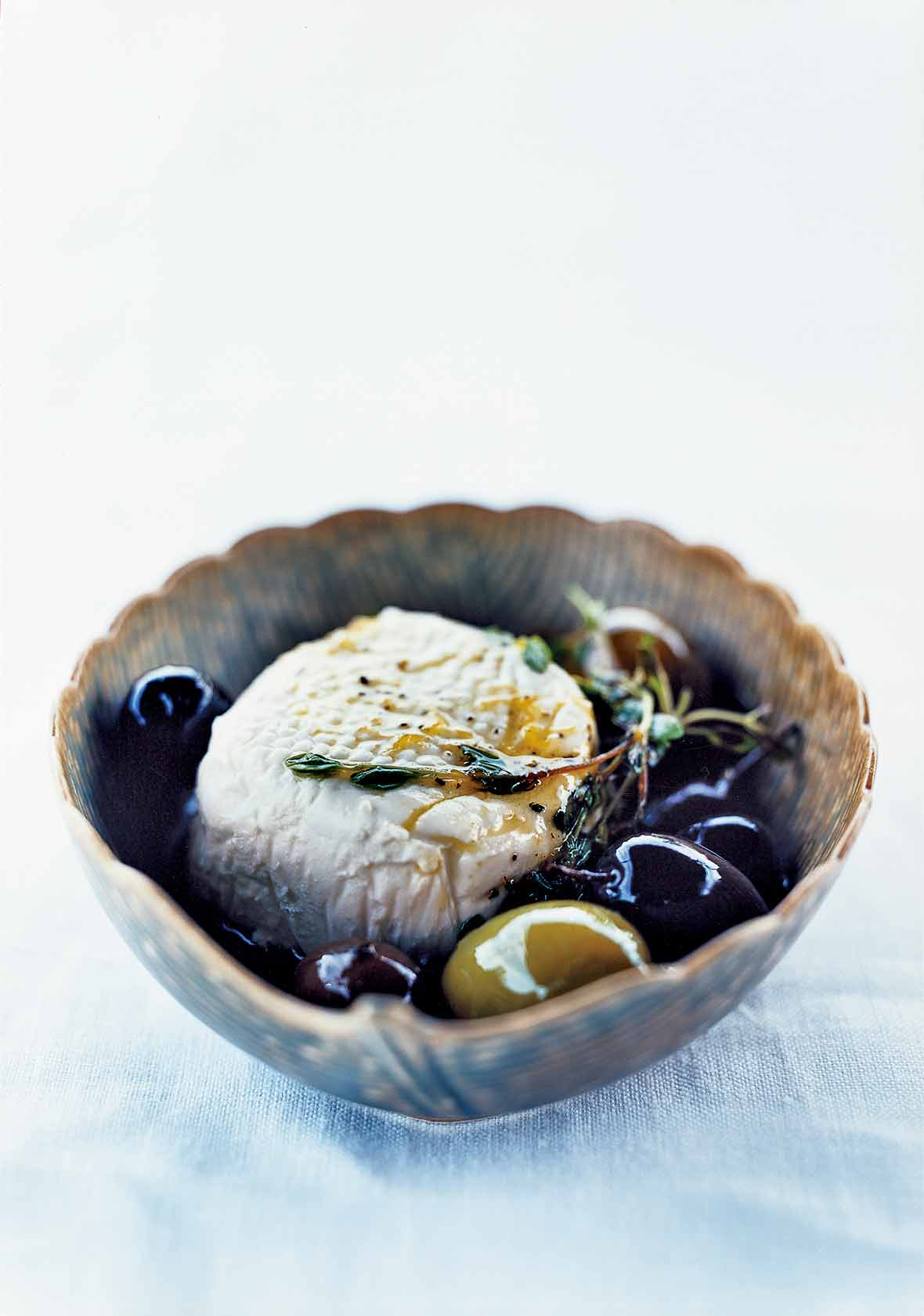 A decorative bowl filled with a sphere of goat cheese and a few olives, topped with a thyme sprig.