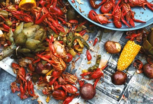 A newspaper-topped table strewn with crawfish, corn, peppers, and potatoes - a classic crawfish boil.