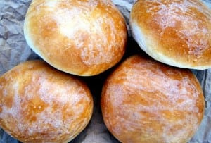 Four homemade hamburger buns dusted with flour on grey paper.