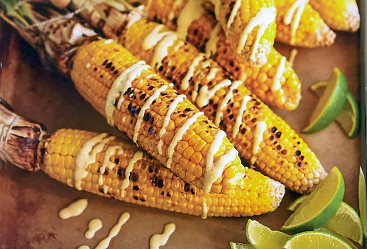 Six ears of grilled Indian corn drizzled with curry yogurt and lime wedges on the side.