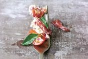Fork with lobster salad and tomato salad, two small leaves of basil