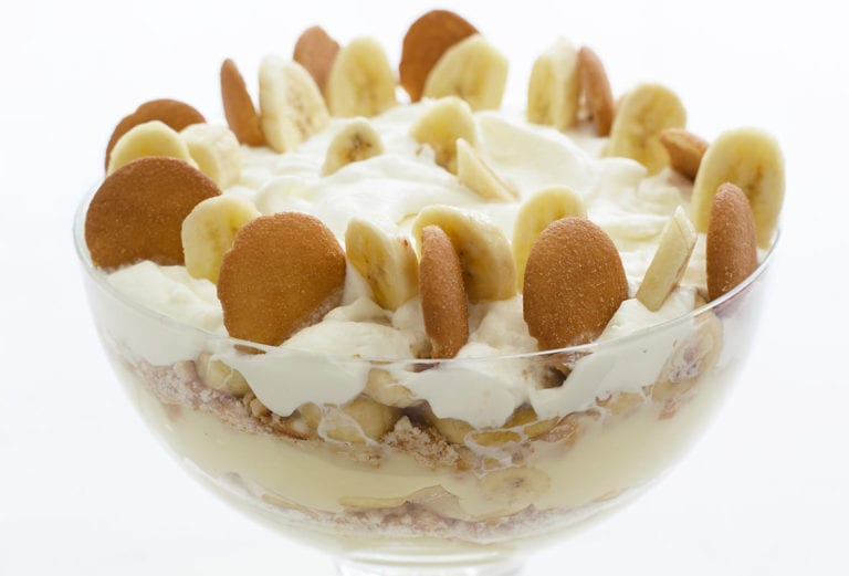 Big glass bowl of layers of vanilla wafer banana pudding topped with sliced bananas, Nilla wafers, and whipped cream