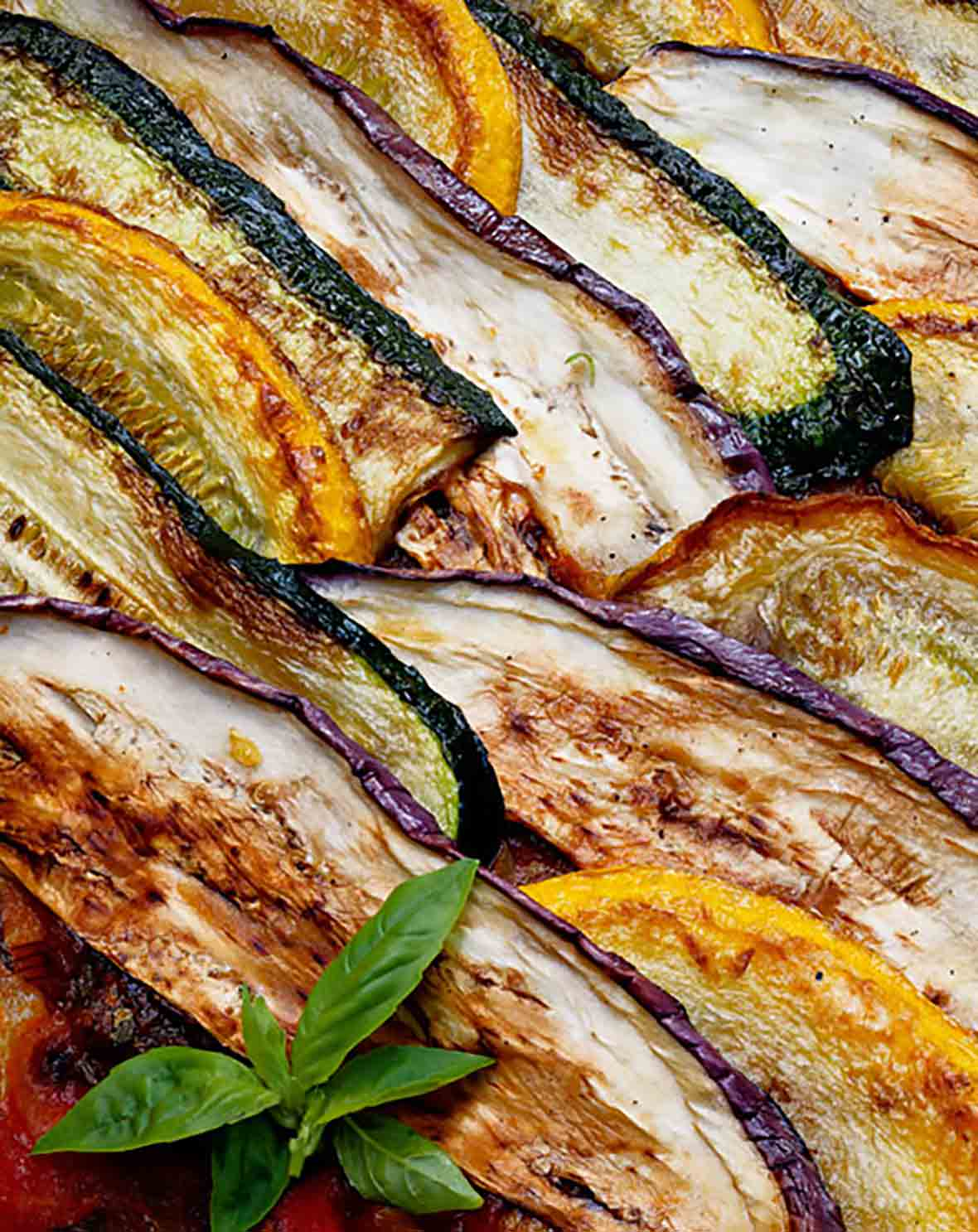 Layers of zucchini, summer squash, and eggplant cooked together and garnished with basil for this summer vegetable gratin.