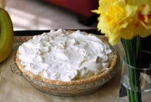 A banana cream pie, topped with pillowy meringue in a glass pie dish with a vase of daffodils beside it.