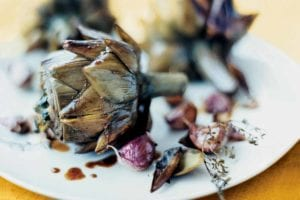 Three braised artichokes with garlic and thyme on a white plate.