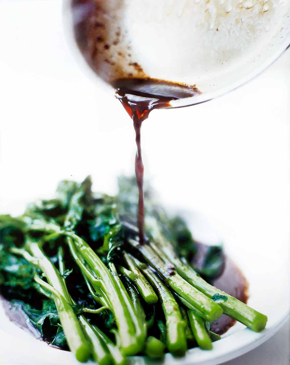 A white plate of broccoli rabe with balsamic brown butter being poured on top