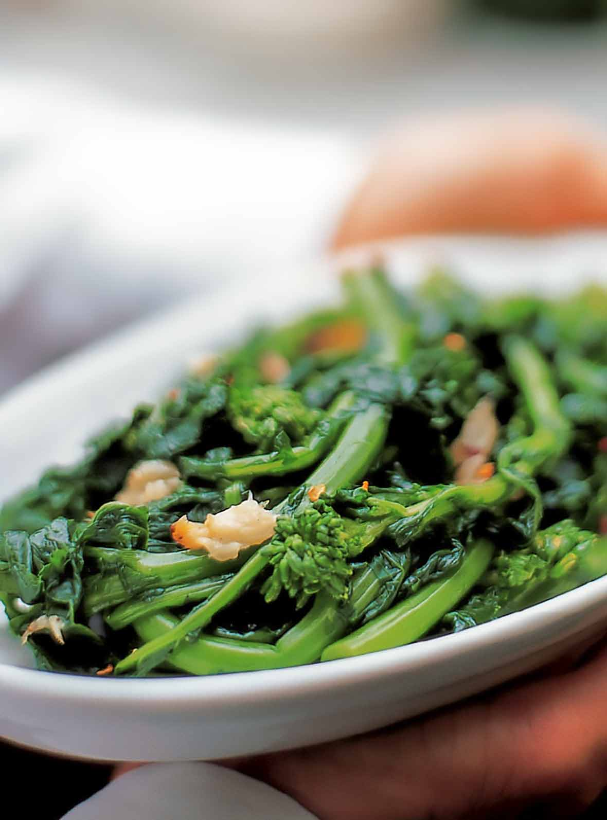 A white platter filled with broccoli rabe, topped with roasted garlic and red pepper flakes.