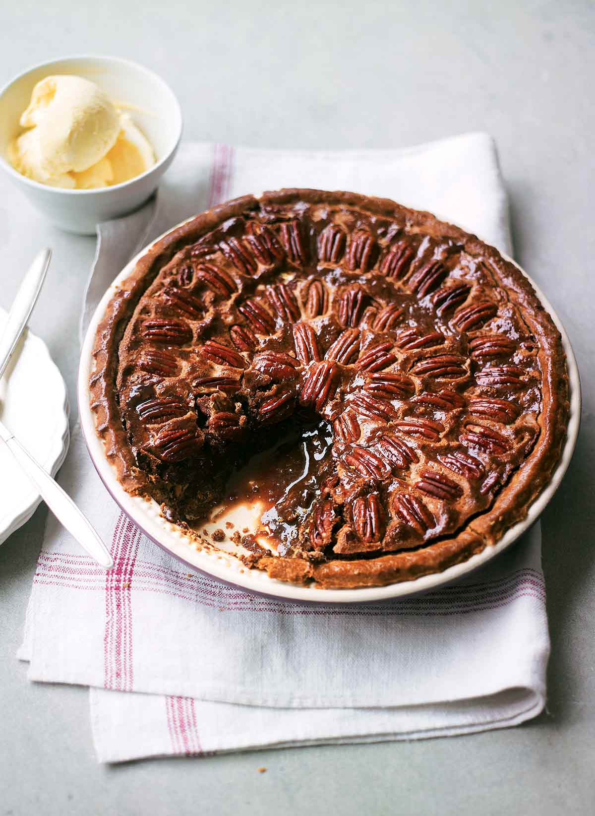 A chocolate pecan pie in a ceramic pie plate with one slice missing on a linen napkin.