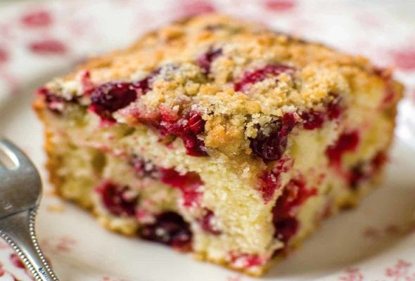A square of cranberry buckle with a streusel top and studded with cranberries.