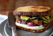 A grilled sausage sandwich with strips of grilled zucchini, red onion, and a herb mayo on a silver plate with a knife resting beside it.