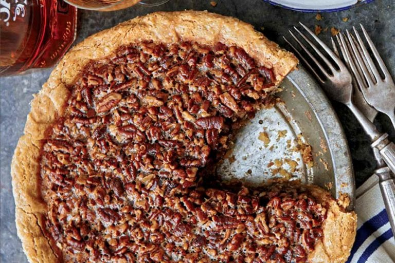 A maple pecan pie in a metal pie plate with one slice missing and forks, plates, and a bottle of rye whiskey beside the pie.