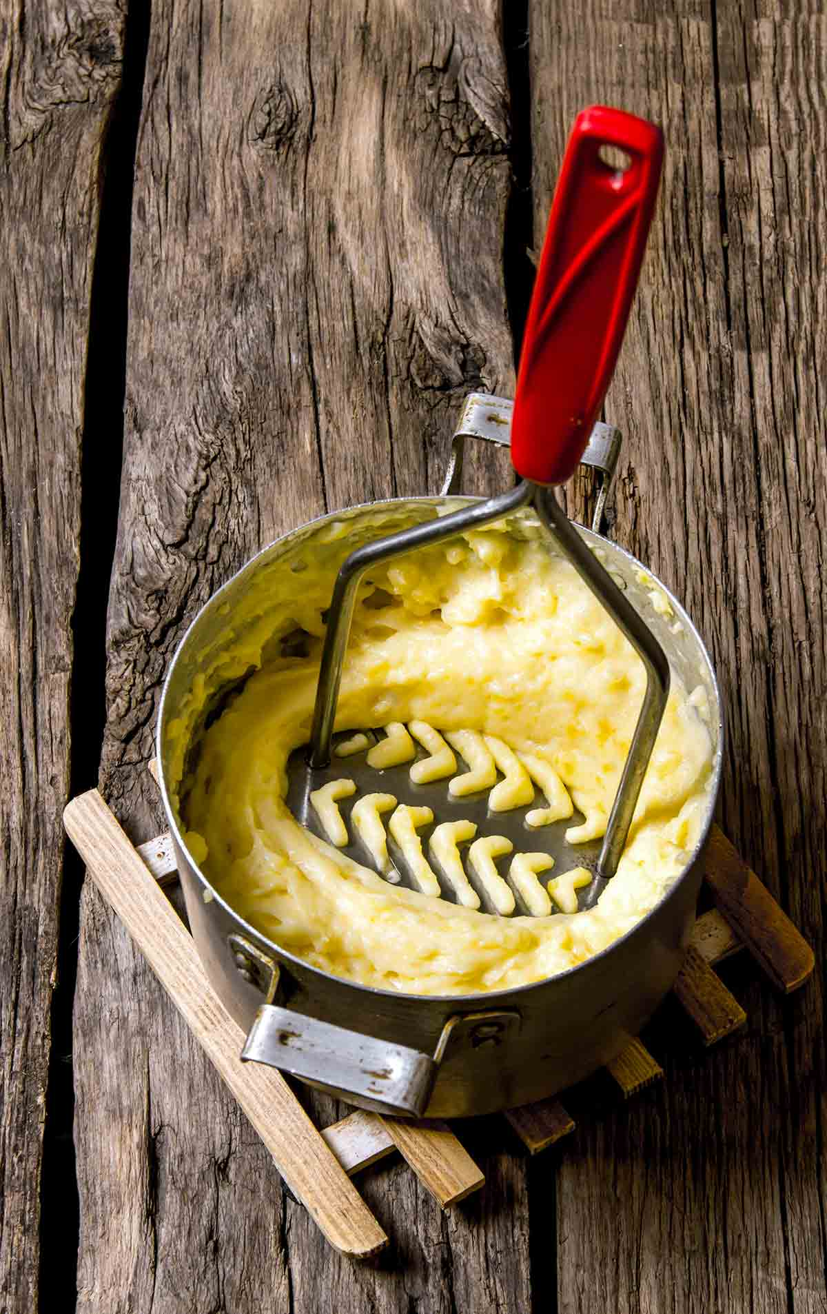 A potato masher pressing down in a pot of olive oil mashed potatoes.