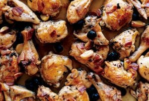 Tray of roast chicken pieces with pancetta, olives, and garlic cloves