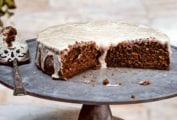 A cut root beer cake on a pewter platter with a slice on a decorative plate in front.