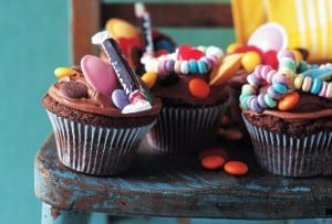 Three sweetie cupcakes, topped with assorted candies and chocolate frosting on a blue chair.