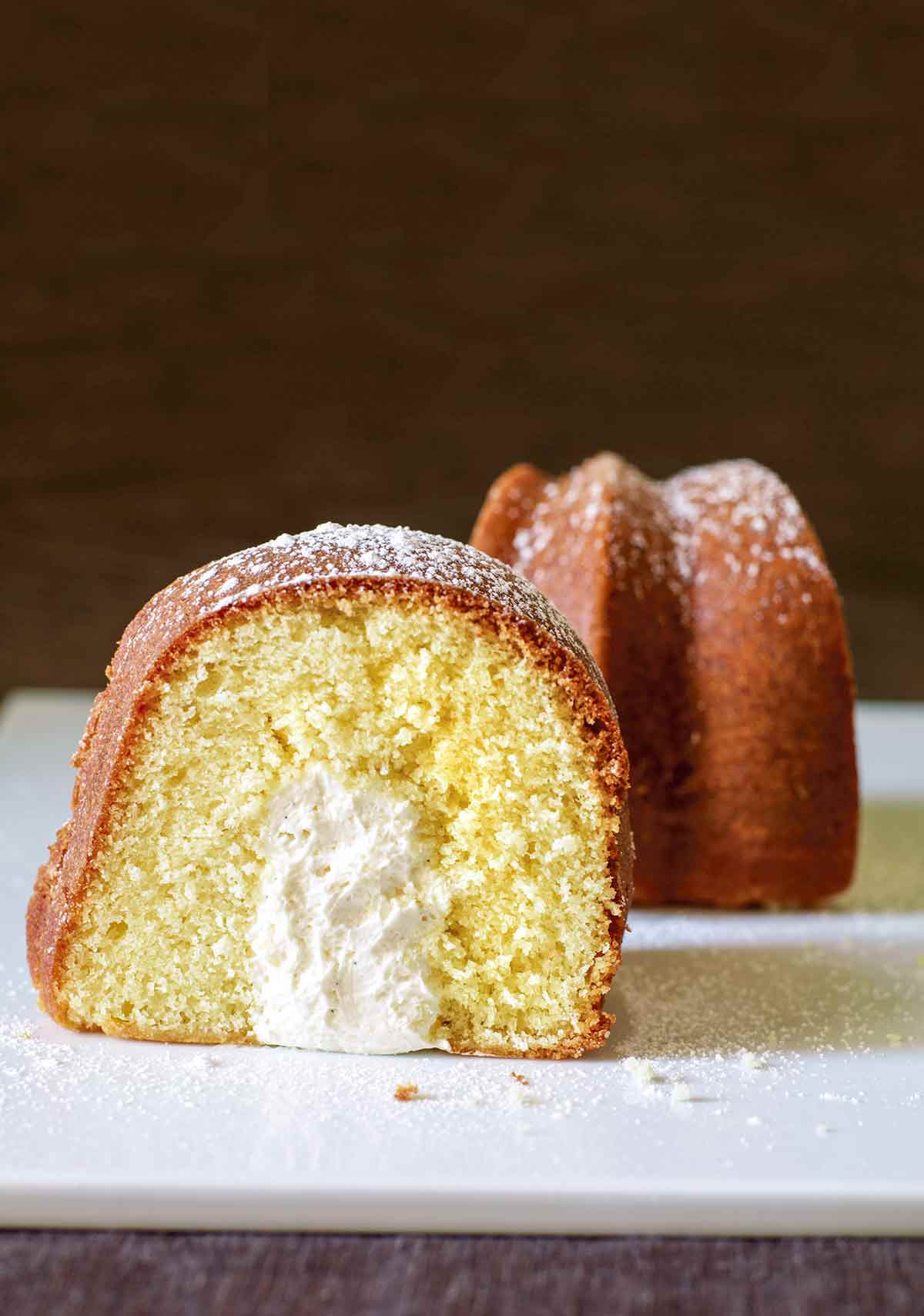 A slice of twinkie bundt cake dusted with confectioners' sugar and turned to show the cross section.