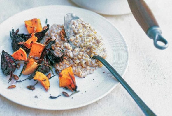 A plate of whole spelt risotto with butternut squash and beets, with an enamel pot of risotto beside it.
