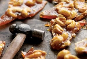 Pieces of broken cashew brittle with a hammer lying beside them.