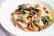 A white bowl filled with chestnut pasta, wild mushrooms, and Brussels sprouts.