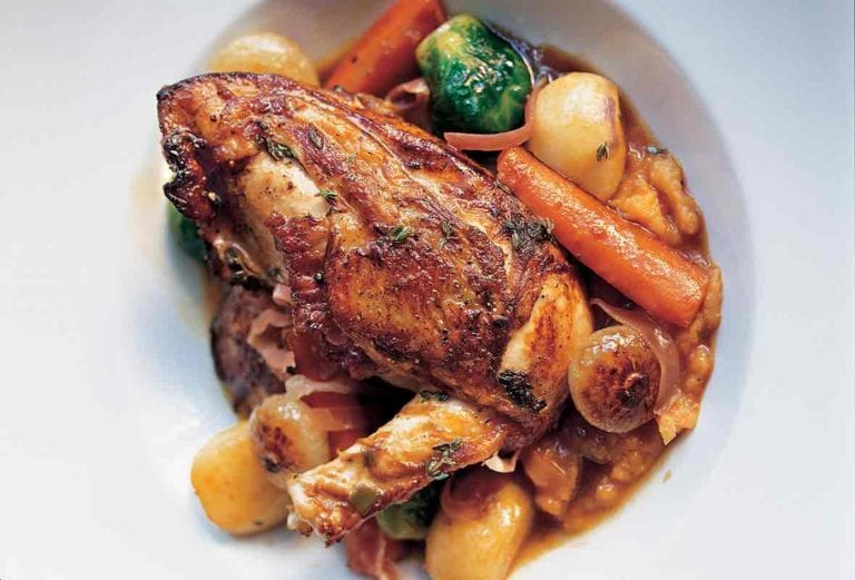 A large white serving bowl filled with chicken with autumn vegetables and Madeira wine.