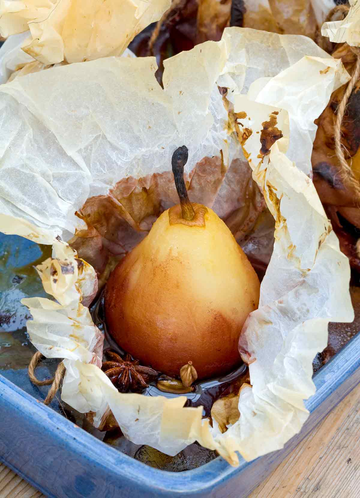 A whole peeled pear in an opened piece of parchment with star anise and cardamom in a blue baking dish.