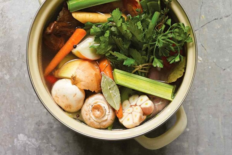 A stock pot filled with mushrooms, leeks, garlic, onion, carrots, and parsley for making roast chicken stock.
