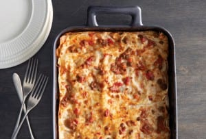 A metal casserole dish filled with a cooked lasagna Bolognese, with three forks and a stack of plates beside it.