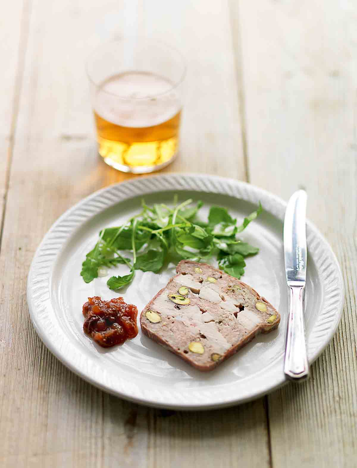 A white plate topped with a slice of chicken, pork, and pistachio terrine, a dollop of chutney, some arugula leaves and a knife.