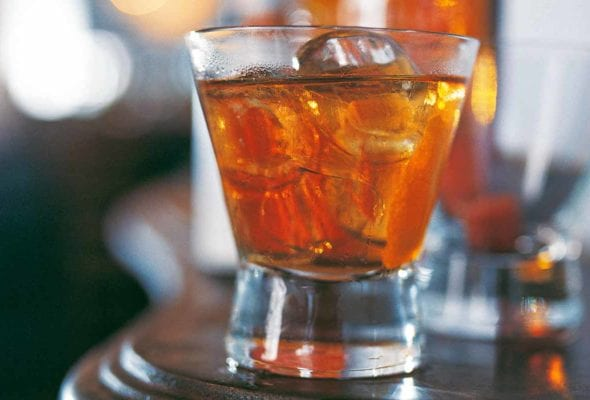 A highball glass filled with classic old-fashioned cocktail and large ice cubes.