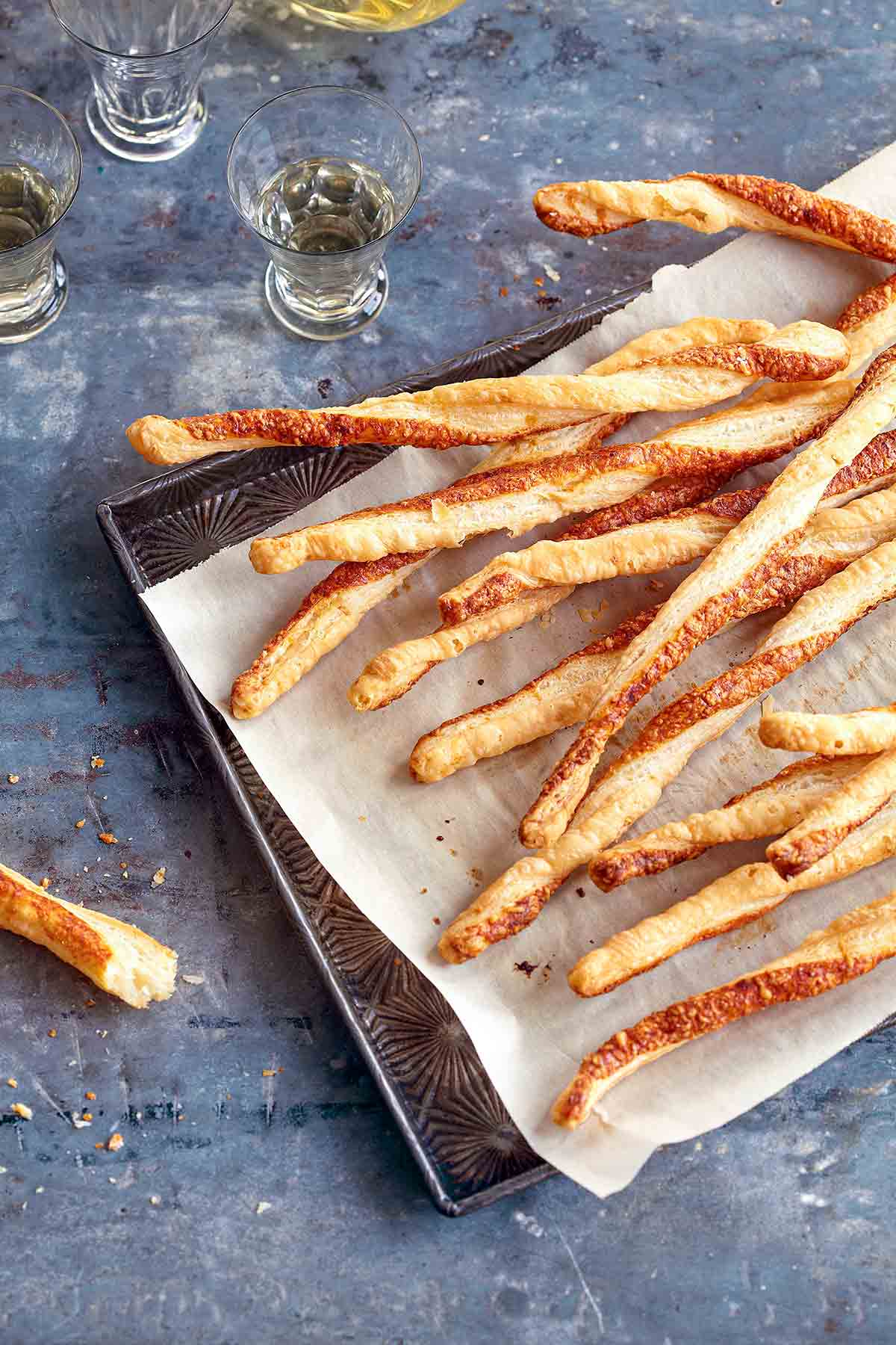 A layer of parmesan twists on a parchment-lined baking sheet.