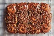 12 schnecken, pecan cinnamon buns, covered with pecan-caramel topping, and chopped pecans on a wire rack