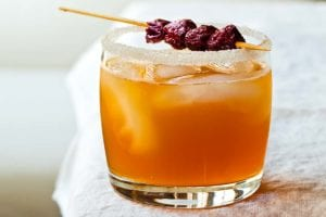 A highball glass with a sugared rim is filled with sidecar cocktail, ice cubes and a dried cherry garnish.