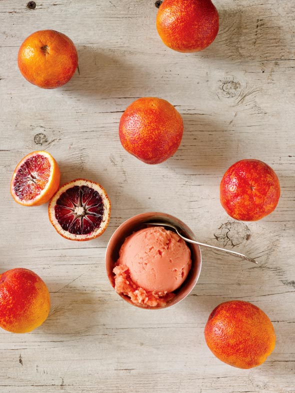 A bowl with a scoop of blood orange sorbet and a spoon in it, surrounded by several blood oranges.