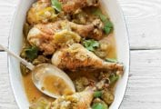 White oval dish with four chicken drumsticks, chopped green tomatillos, cilantro, onion, sliced chiles