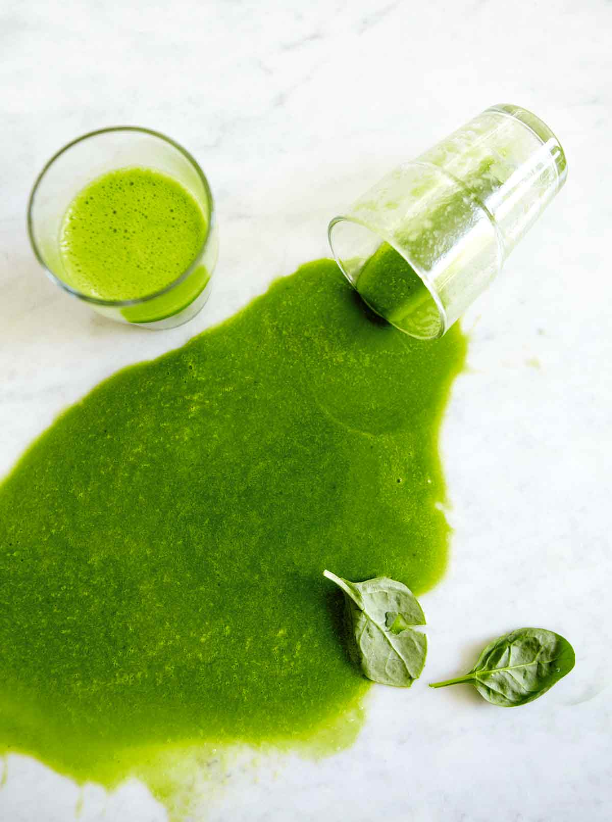 A glass of green smooth and a second glass that is on its side with green smoothie poured out.
