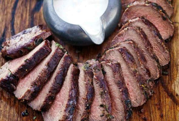 A wooden cutting board topped with sliced loin of grilled venison with horseradish cream sauce on the side.