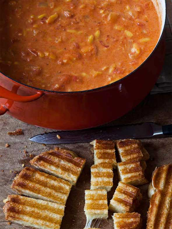 A red Dutch oven filled with easy tomato soup and a pile of grilled cheese croutons on the side