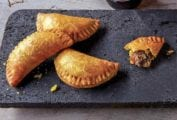 Five half-moon pastries, Jamaican beef turnovers, on a stone plate, three bottles of beer