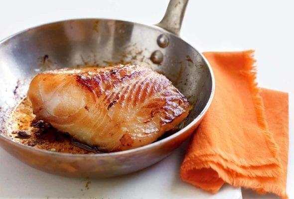 A piece of cooked miso cod in a stainless steel skillet that is resting on a white board next to an orange napkin.