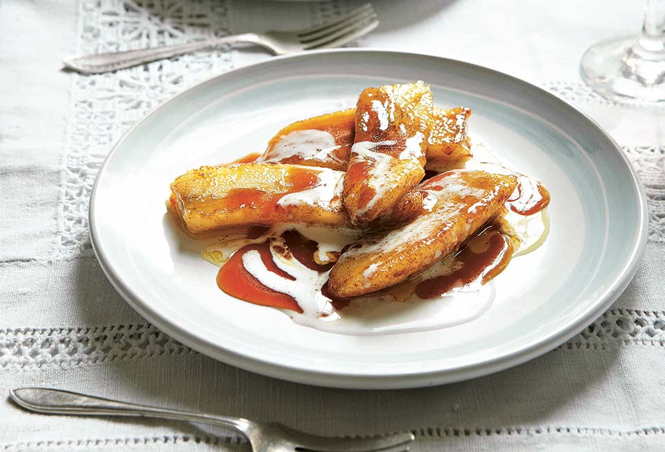 A white plate of pan-fried bananas with brandy that have been drizzle with coconut cream with a fork resting on either side.